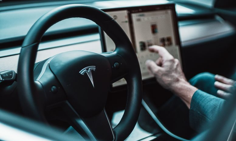 The interior of a Tesla vehicle with a driver using its screen.