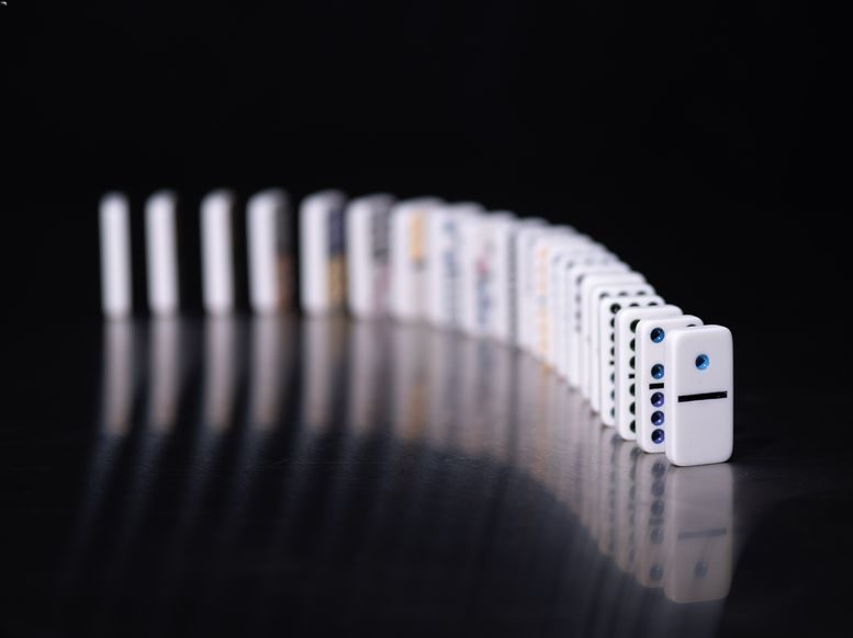 Dominos set up on a surface against a black background.