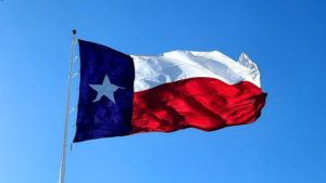 The Texas state flag waving in a blue sky